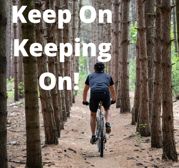 Cyclist in a endless forest with words Keep On Keeping On