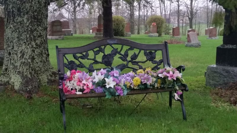 wooden bench with seat covered by flowers in the cemetery