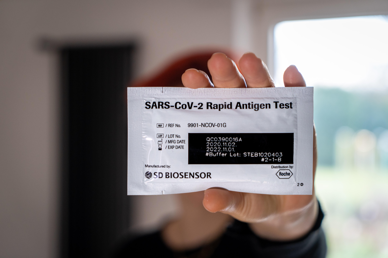 Hand holding a rapid antigen swap package